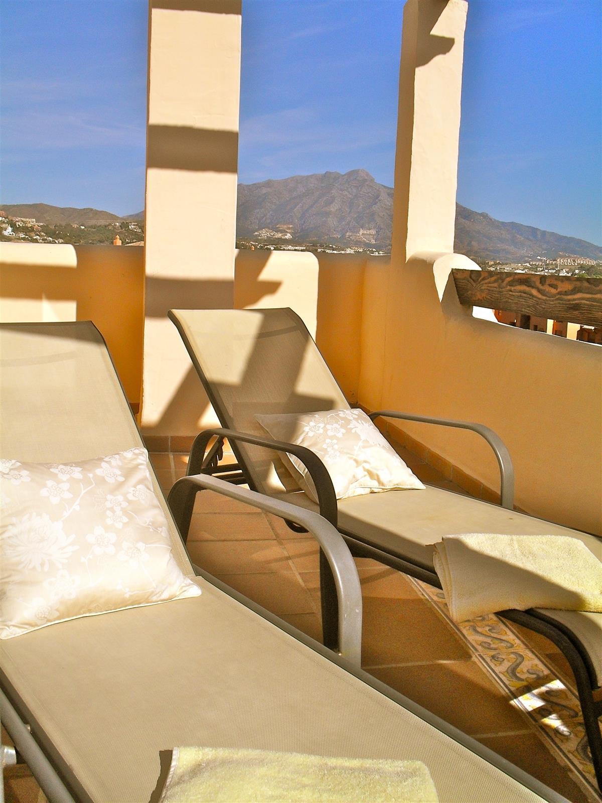 Large SE facing terrace with sun loungers and mountain views