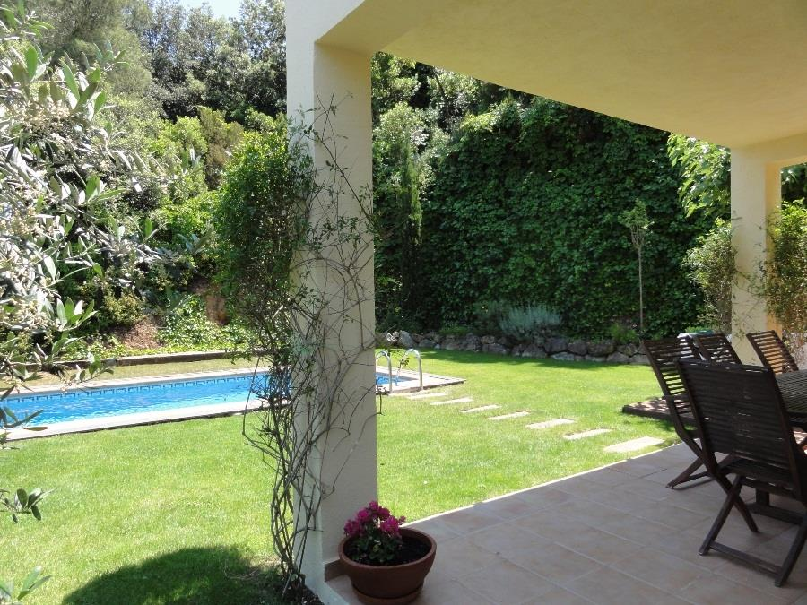 view from covered dining terrace to garden and pool