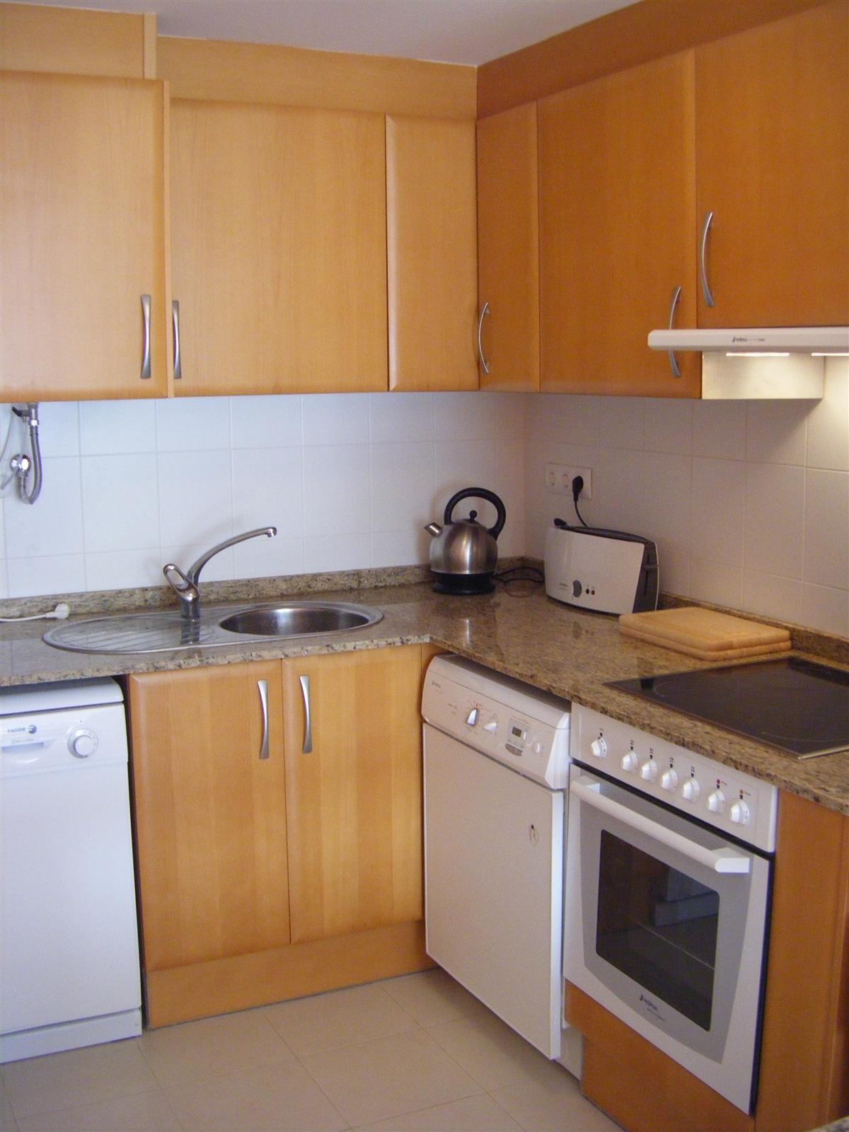 The kitchen with dishwasher, washingmachine, oven and ceramic hob.