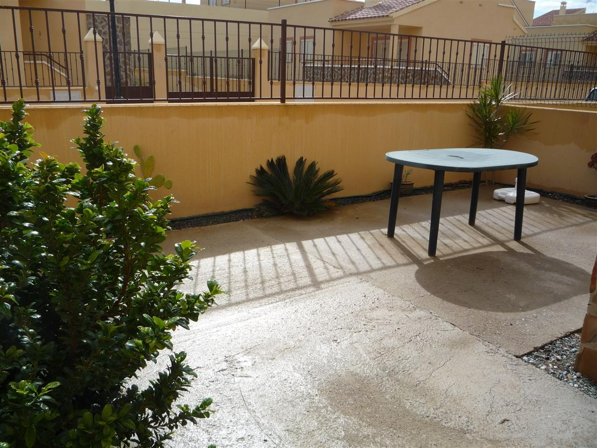 Patio below balcony - concreted with a few shrubs.