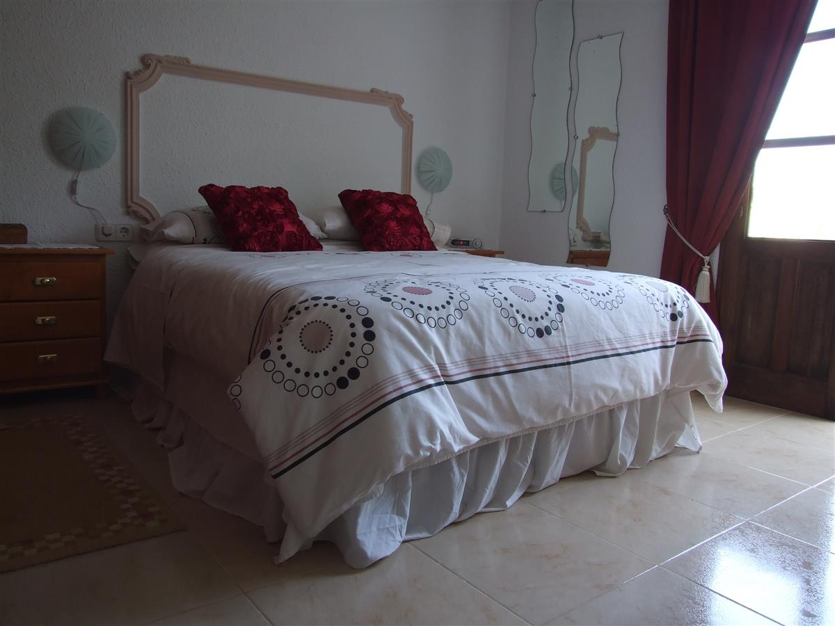 Main bedroom with double bed and french doors opening onto garden.