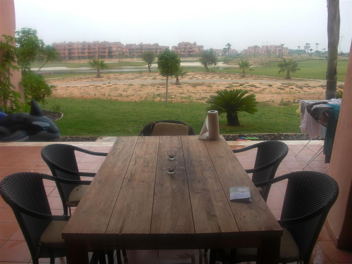 view from livingroom to terrace, golf course and lake