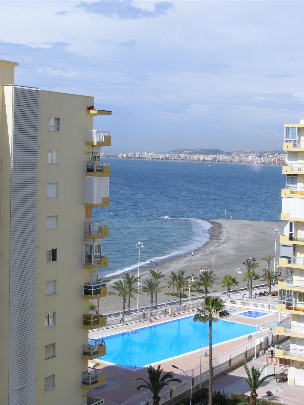 The view from the balcony showing the communal pool and beach