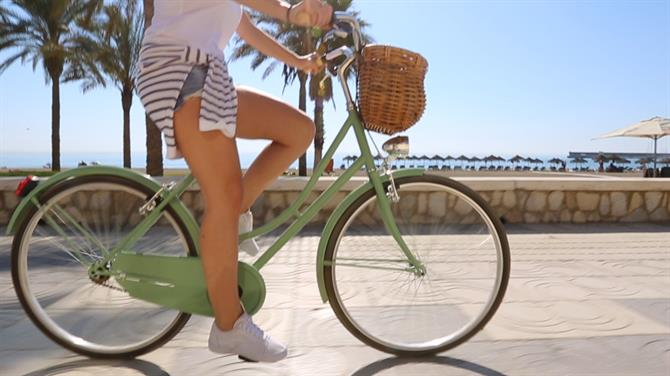 Girl cycling along the Paseo Maritimo in Malaga