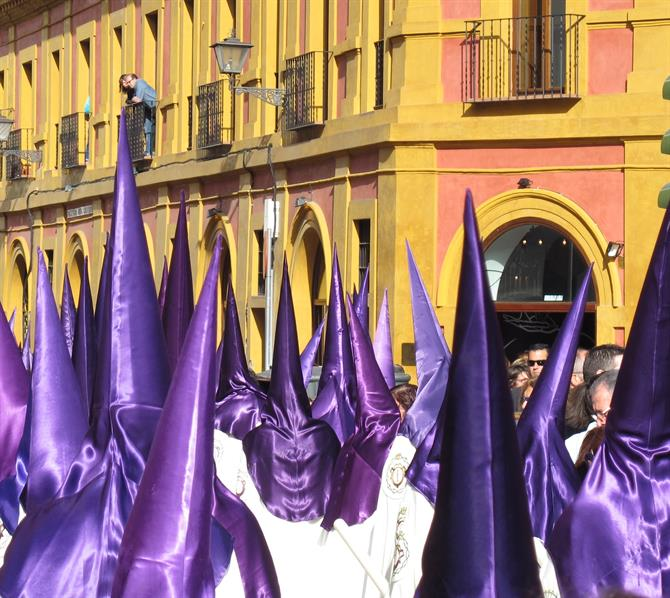 Purple-robed nazarenos in Semana Santa procession