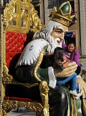 Giggling girls sit on the massive majestic King in Alicante province