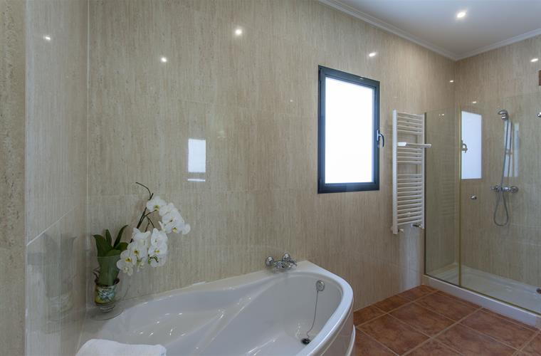bathroom with bath, shower and marbles