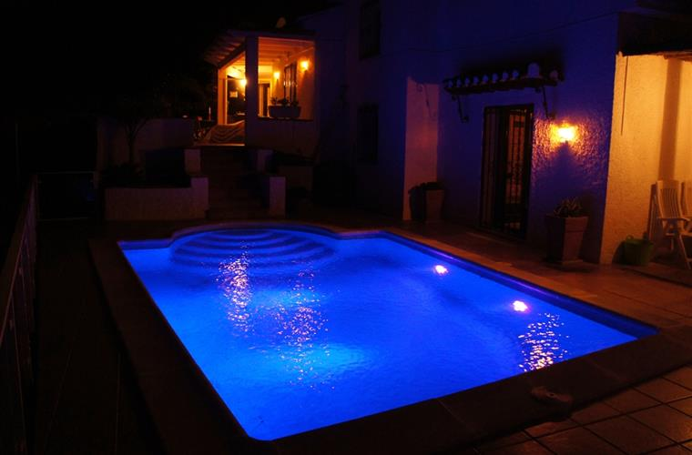 Multi coloured swimming pool lights by night