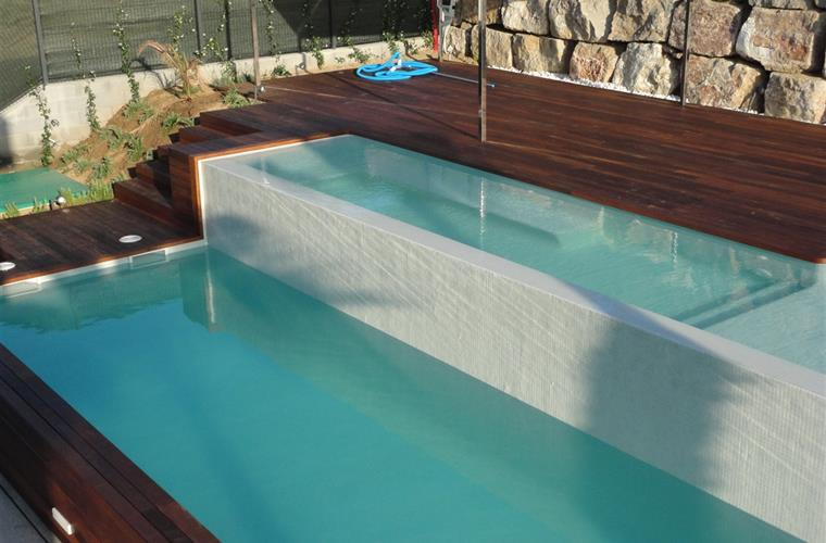 Swimming pool with chill out area sofas and lounge chairs