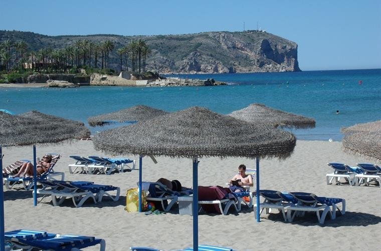 Thatched parasols and loungers to hire on Javea bay's Arenal beach