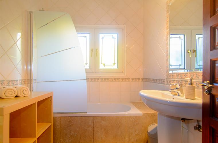 En suite bathroom with bathtub and shower