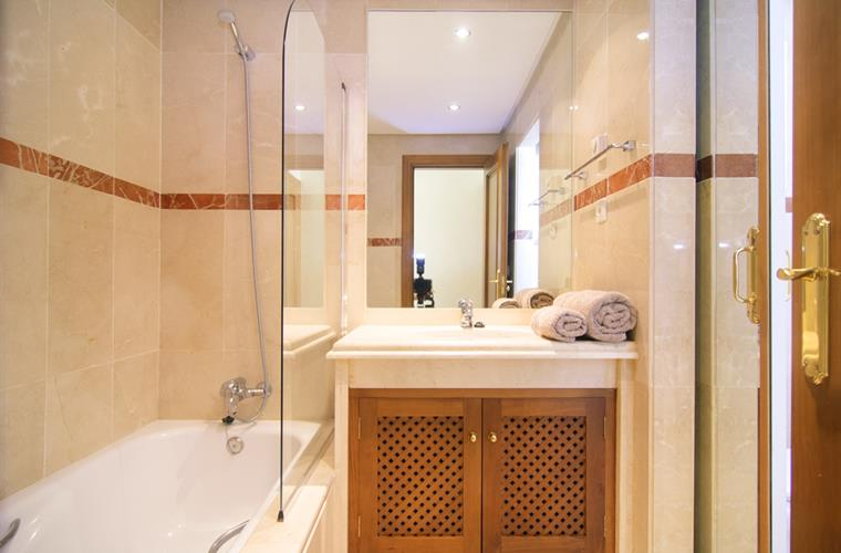 En suite bathroom with bathtub with shower, sink