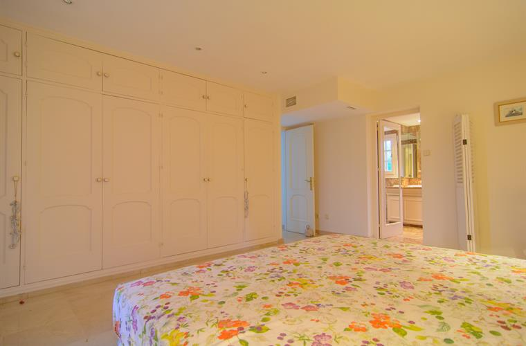 Master bedroom with large wardrobes and lamps
