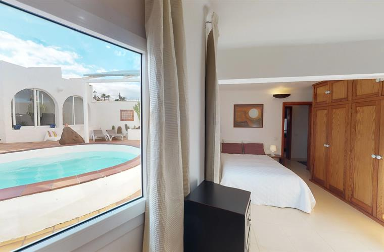 2nd bedroom with views of the pool and patio