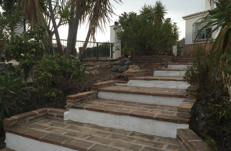 Villa, gate, driveway, gardens and steps down to the pool