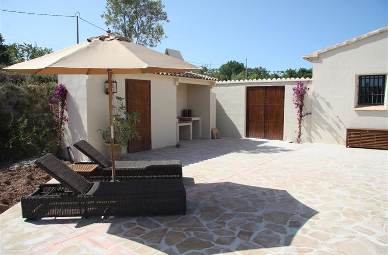 Sunny terrace with large parasol and comfortable pool chairs.