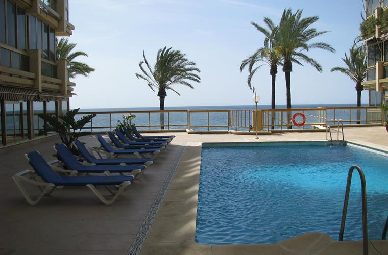 Pool with free sun beds with stairs to the sea