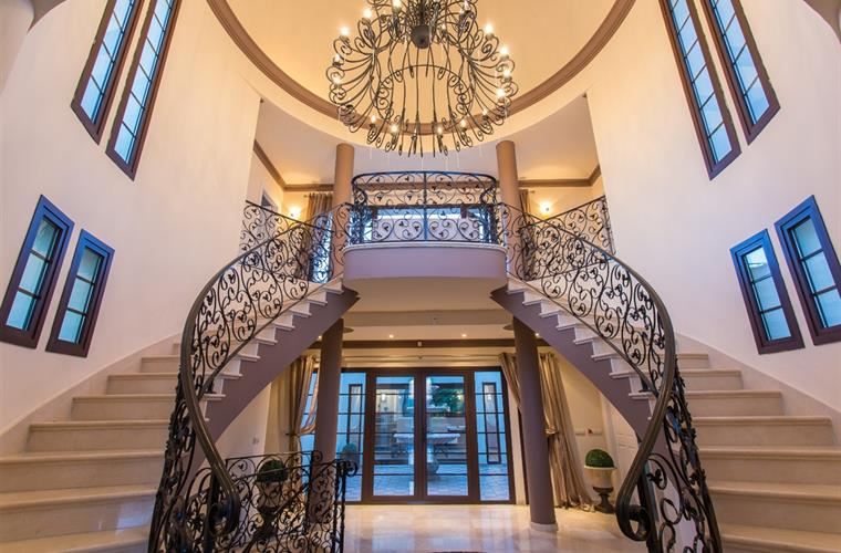 Sweeping double staircase and chandelier