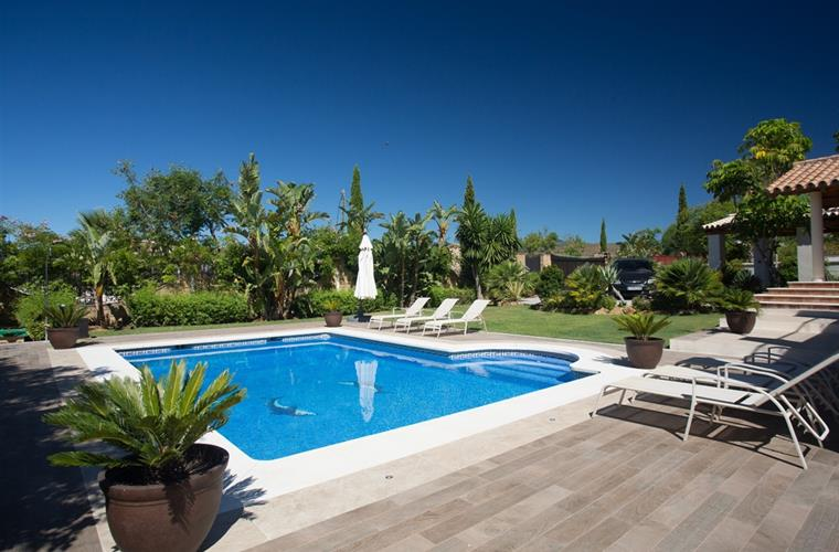 The pool and tropical gardens at Villa Marco, Marbella