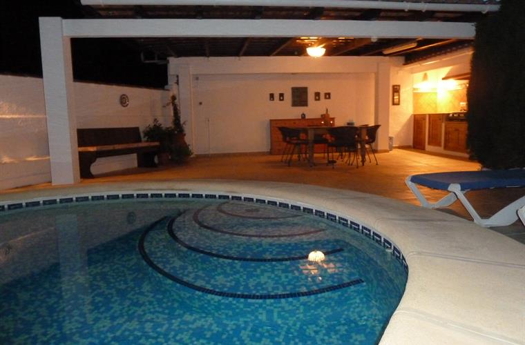 pool and outdoor kitchen at night