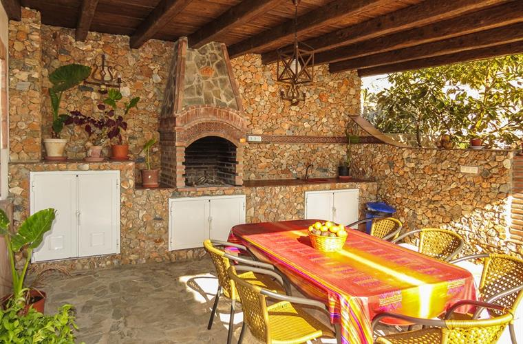 The covered terrace in the entrance area and the brick barbecue