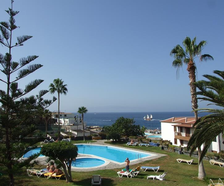 view from the balcony of the garden, main pool and sea beyond