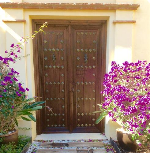 Huge wooden front door surrounded by Bouganvillea.