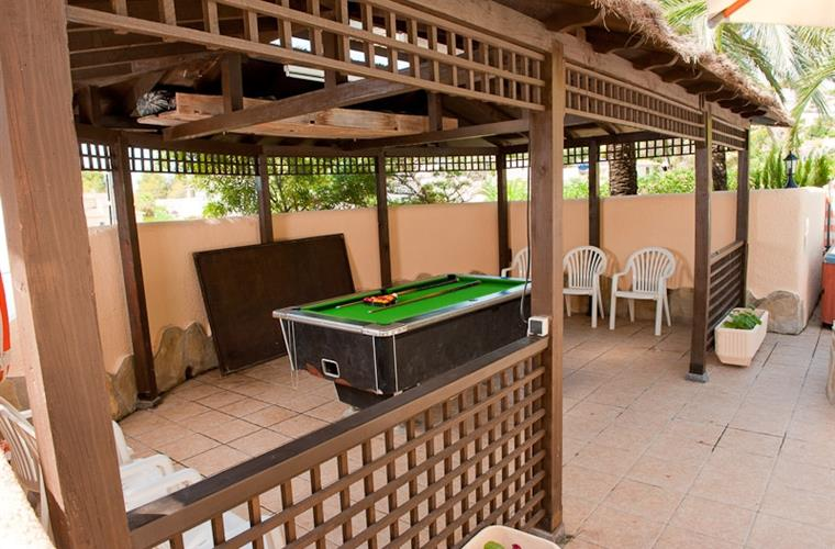 The pool table and gazebo next to the pool area