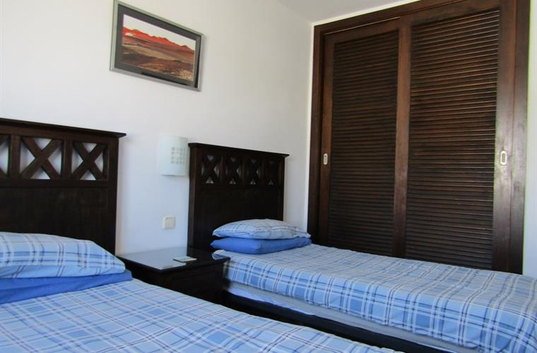 Bedroom 2 has stylish furniture and 2 single beds