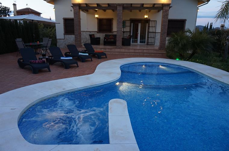 Outside area with jacuzzi and sun loungers at sunset.