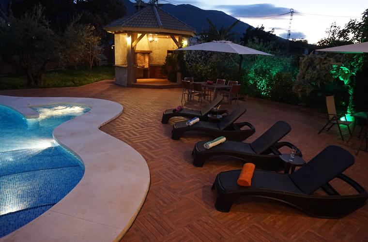 Outdoor area of sun loungers at sunset and lighting.