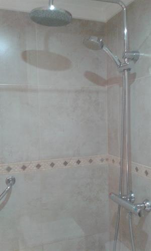 Twin headed shower unit with hand rail for assistance if needed.