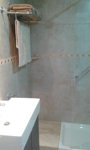 Newly tiled bathroom.Washer is situated as you enter the bathroom.