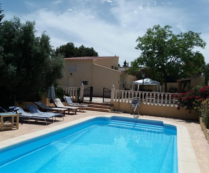 Large heated swimming pool with sunbeds separate from terrace