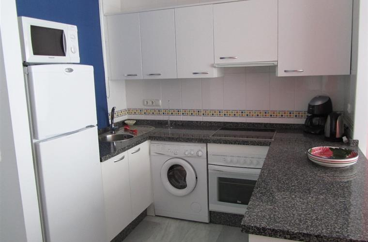 Kitchen with washing machine, dishwasher, oven, hob, microwave.