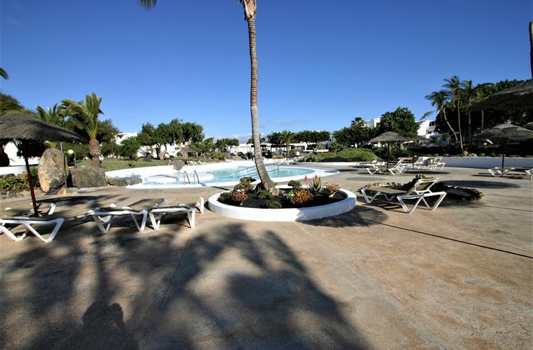 spacious sunbathing areas around pool with shade cover