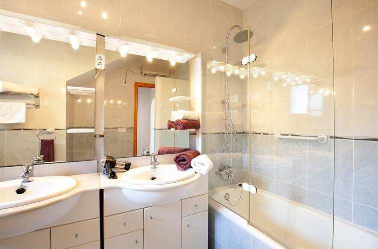 Spacious bathroom with double vanity and bathtub with rain shower