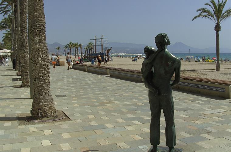 boardwalk on the beach with bronse sculptures , palm threes, ...