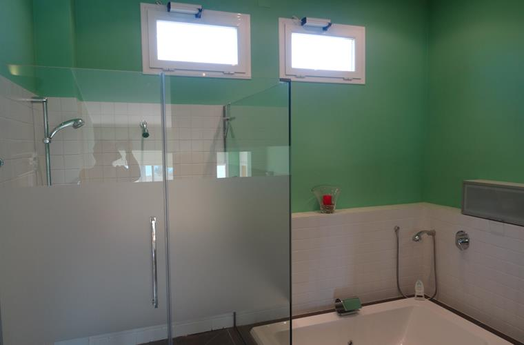 Green bathroom with shower, whirlpool and ocean view