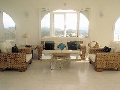The living room has Mediteranean furniture and views.