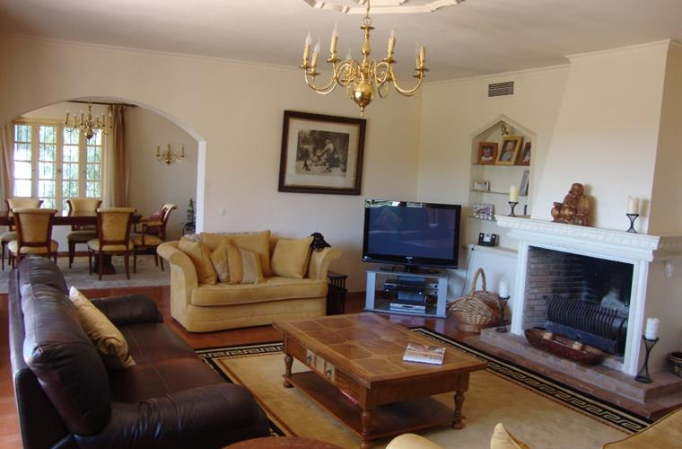 lounge with 3 sofas, large open fireplace dining room thro archway